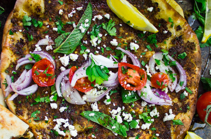 close up of a turkish piza lahmacun topped with herbs, tomatoes, onions, lemon slices and feta cheese