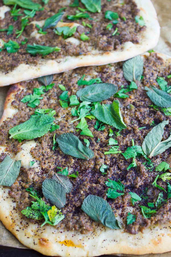 Freshly baked Turkish Pizza Lahmacun topped with fresh herbs and greens