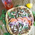 Spicy Turkish Pizza Lahmacun sprinkled with crumbled cheese, fresh herbs, onion slices and tomatoes