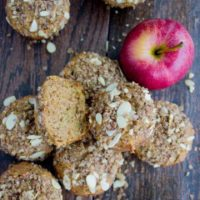 Whole Wheat Apple Cinnamon Muffins with Almond Crumb Topping arranged on a wooden tabletop with an apple in the background