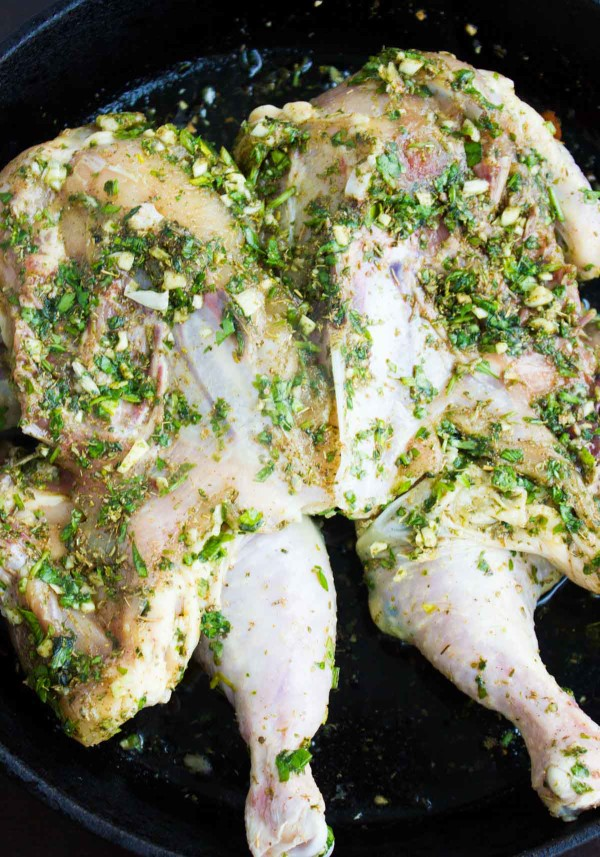 a whole butterflied chicken smothered with herb butter in a black skillet ready to be cooked