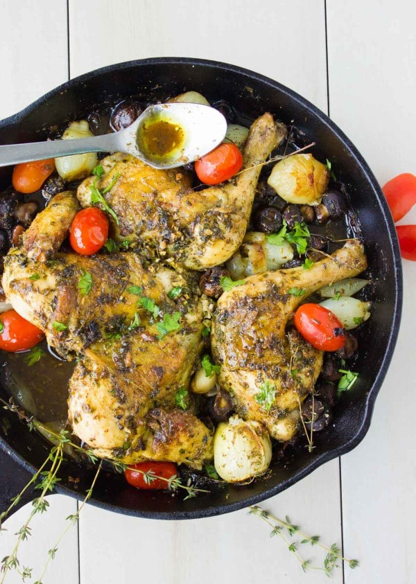 Butterflied Garlic Herb Roast Chicken served in a black skillet with some pearl onions, mushrooms, blistered tomatoes and fresh herbs