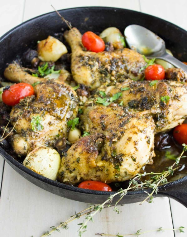 Garlic Herb Roast Chicken served in a black skillet with some blistered tomatoes and fresh herbs