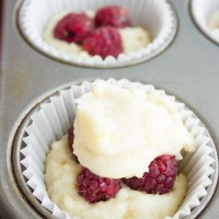close-up of a unbaked muffins with fresh raspberries peaking out of the batter.