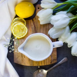 The tahini sauce in a pouring cu with lemon slices around it and white flowers, and a tea towel