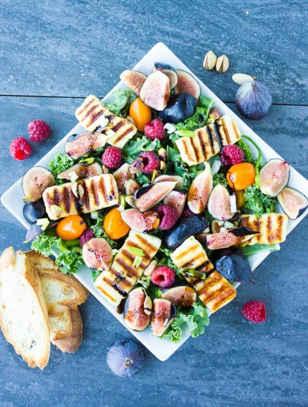 Grilled Halloumi Salad drizzled with balsamic reduction and topped with fresh figs and raspberries on a big white plate placed on a blue rustic table.