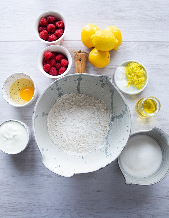 ingredients for the raspberry muffins recipe including flour, baking powder, sugar, lemon zest, oil, egg, yogurt, raspberries