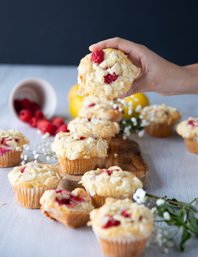 A hand holding a raspberry muffin above a pile of muffins to show the raspberries in tact and the crunch topping