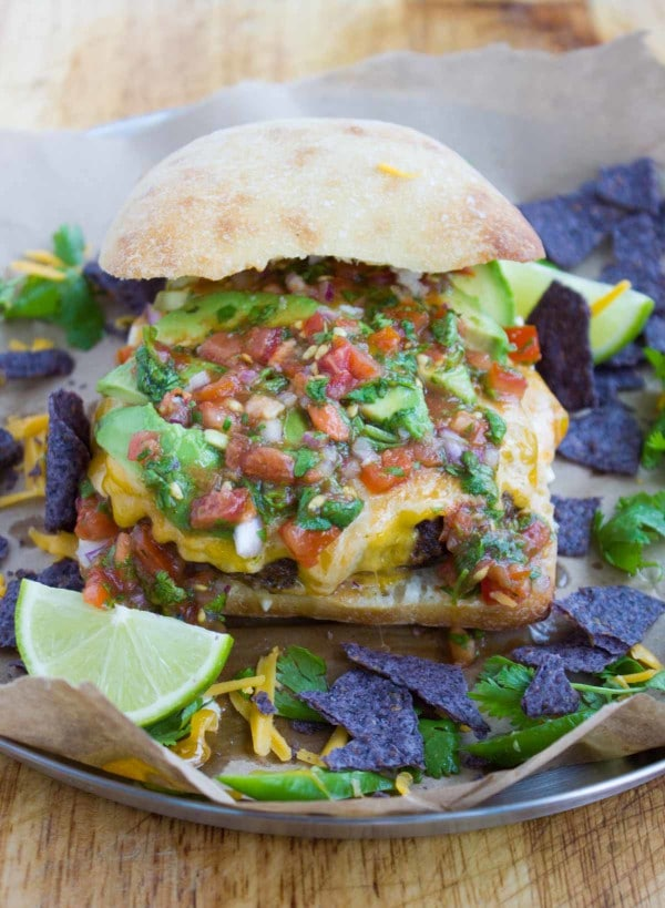 A variety of fajita toppings over the juicy burgers including salsa, guacamole, cilantro, jalapeños, avocados and tortilla chips