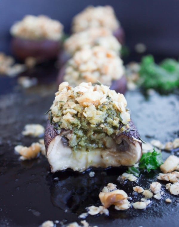 Easy Stuffed Mushrooms with kale pesto and crunchy walnut topping lined up on a black plate