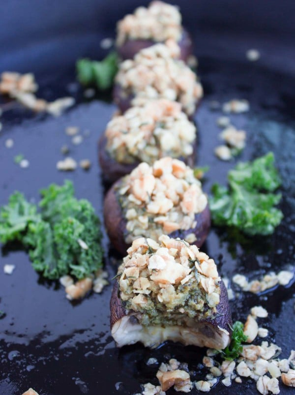 Kale Pesto Stuffed Mushrooms with crunchy walnut topping lined up on a black plate with some kale leaves as decoration