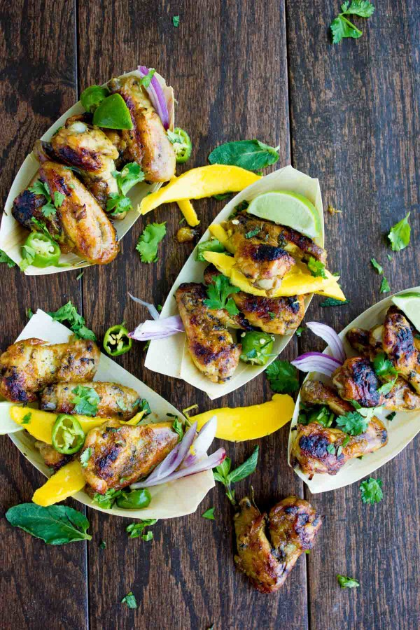 Overhead shot of Sweet and Spicy Chicken Wings smothered in Mango Chutney and served in small paper dishes with some fresh cilantro and mango slices