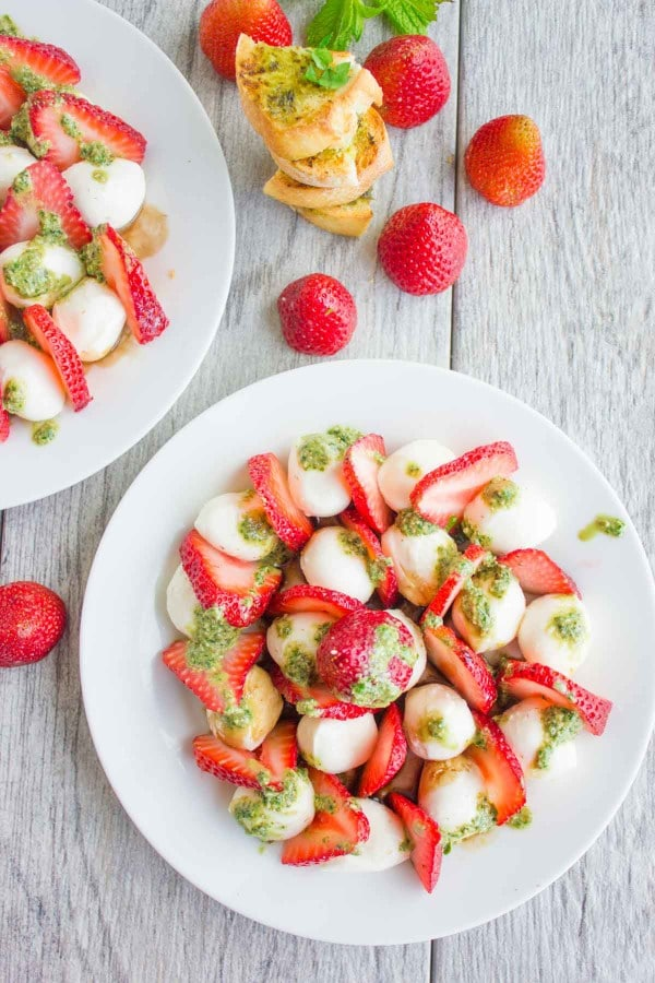 Overhead shot of Strawberry Caprese Salad drizzled with pesto, served on a white plate with baguette slices and whole strawberries in the background.