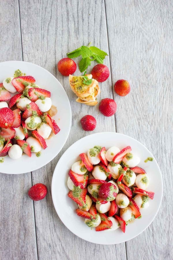 Overhead shot of Strawberry Caprese Salad drizzled with pesto, served on two white plates with baguette slices and whole strawberries in the background.