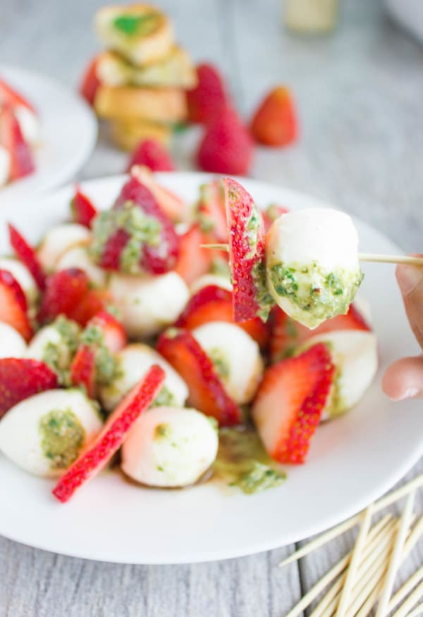 a mini mozzarella ball and a slice of strawberry smothered with green pesto skewered on a toothpick with a plate of Strawberry Caprese Salad in the background.