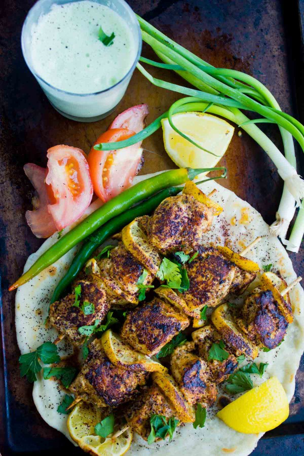 Turkish Style Chicken Skewers served on a big pita, with some veggies and a glass of Ayran in the background