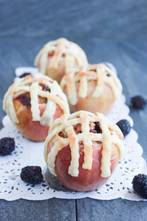 Apple Pie Stuffed Apples with golden brown pie crust lattice on top served on a cake doily