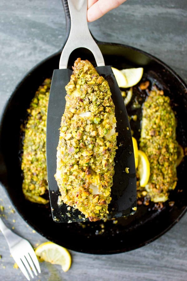 Pesto Pistachio Fish Fillet on a black kitchen spatula held over a skillet with more fish fillets.
