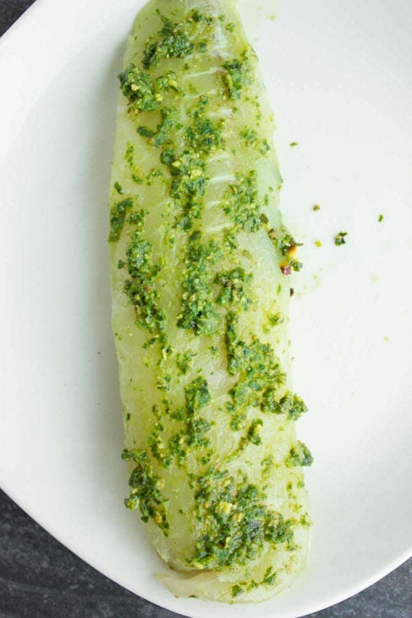 white fish fillet coated with green pesto on a white plate.