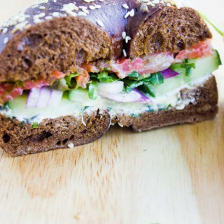 Close up of a bagel breakfast sandwich showing the layering of cream cheese, cucumbers, onions, spinach, smoked salmon and sauce in a pumpernickel bagel