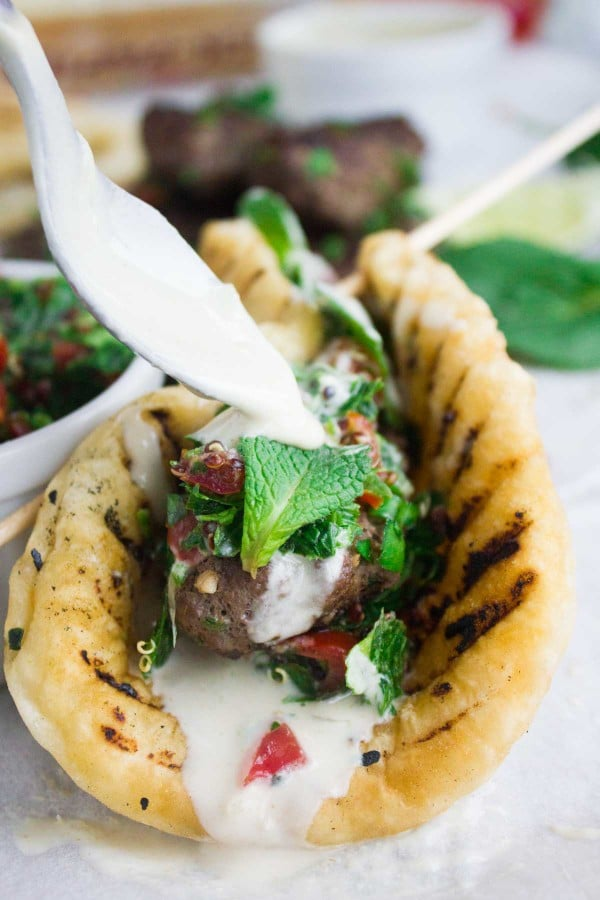 lamb kebab wrap and a spoon drizzling some tahini sauce over the lamb wrap