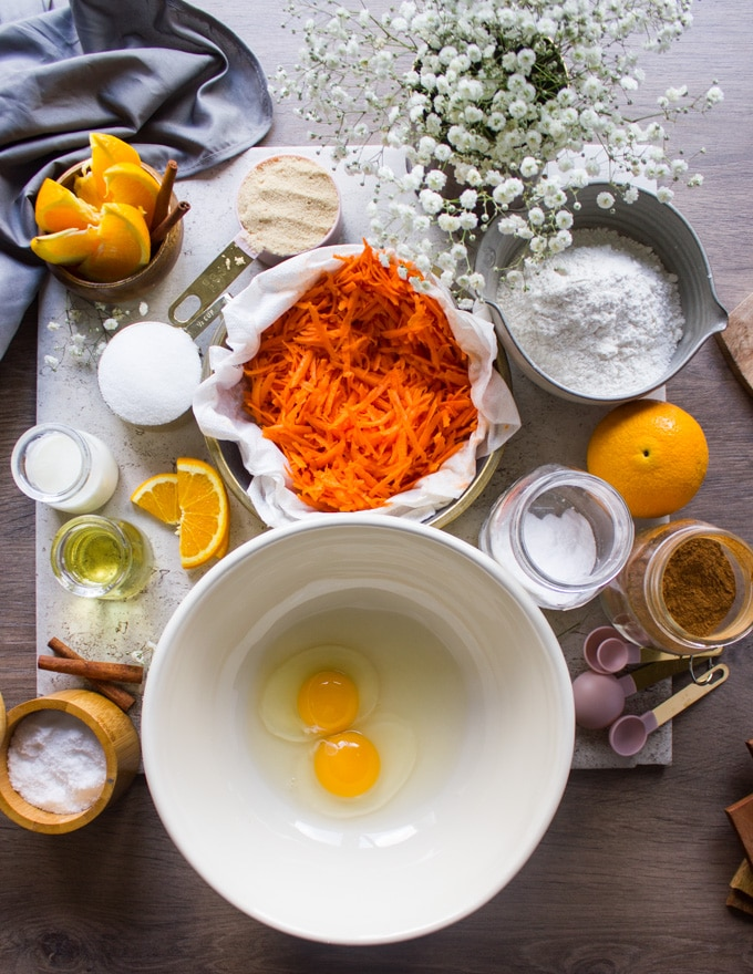 different bowls with ingredients for the carrot cake, a bowl of eggs, a bowl of carrots, oil, a bowl of sugar, a bowl of flour, baking soda, salt, cinnamon, buttermilk, orange juice and some fresh oranges