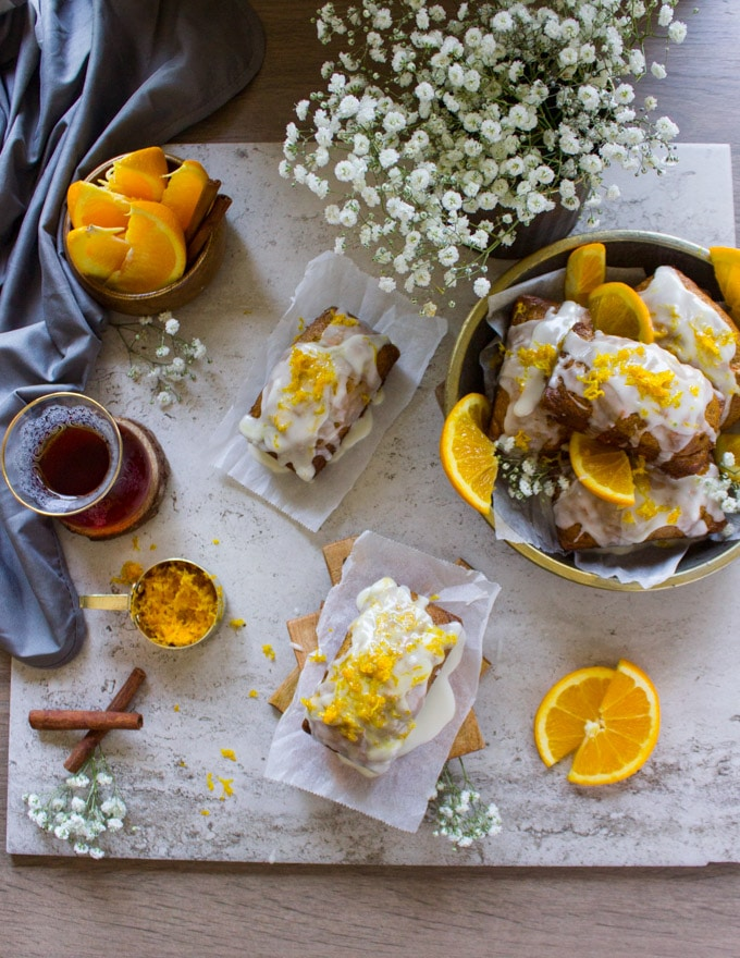 Top view showing a plate of mini carrot cakes, white flowers, a cup of tea, half oranges, cinnamon sticks