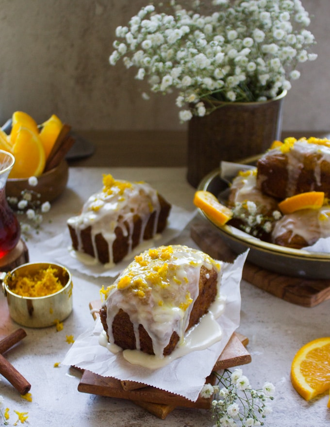 A set of two carrot cake glazed with orange glaze and topped with orange zest.