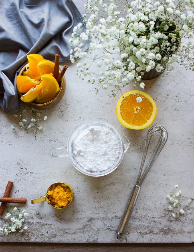 The glaze ingredients. A bowl with the confectioner sugar and a half an orange and a whisk