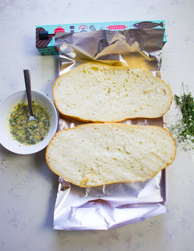 Itlian loaf of bread sliced in half on abaking sheet lined with foil