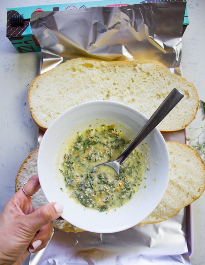 A bowl with a mixture of roasted garlic, butter, herbs and parmesan cheese ready to spread on the bread