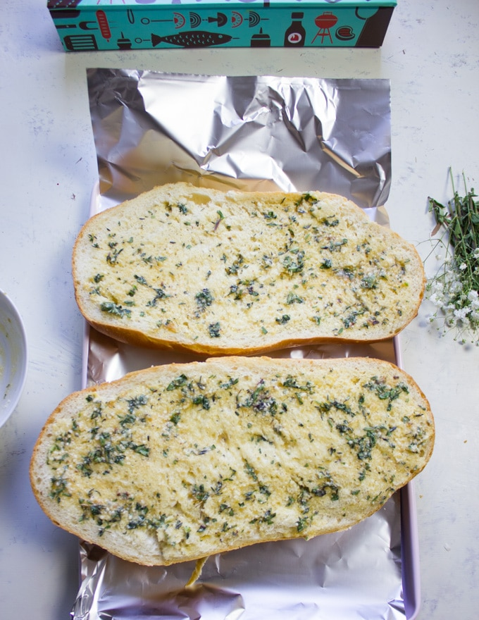 The loaf of spread halves are spread well with the roasted garlic butter mixture and ready to be wrapped