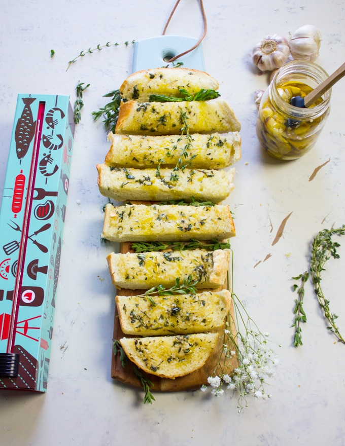The whole loaf of garlic bread sliced on a cutting board with a jar of roasted garlic on the side