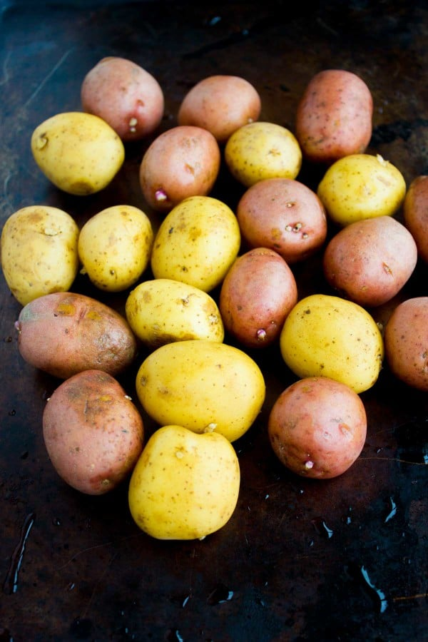 washed red and yellow potatoes arranged on a black baking sheet