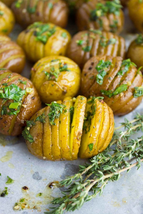 Close-up up Herb Roast Potatoes drizzled with butter and garnished with fresh thyme