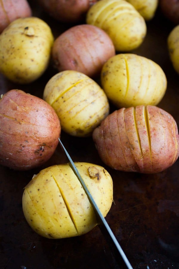 red and yellow potatoes with slits cut into them with a knive
