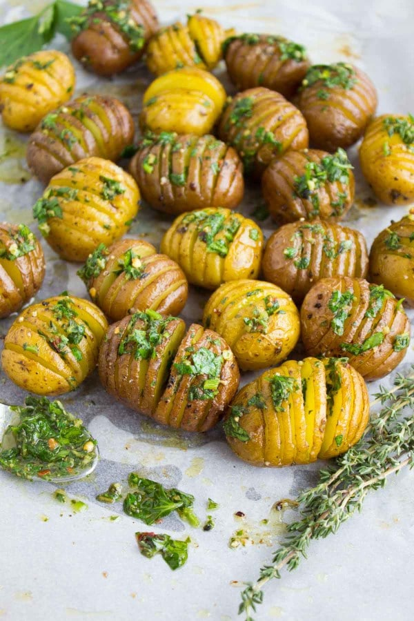 Herb Roast Potatoes smothered with herb butter arranged on a baking tray