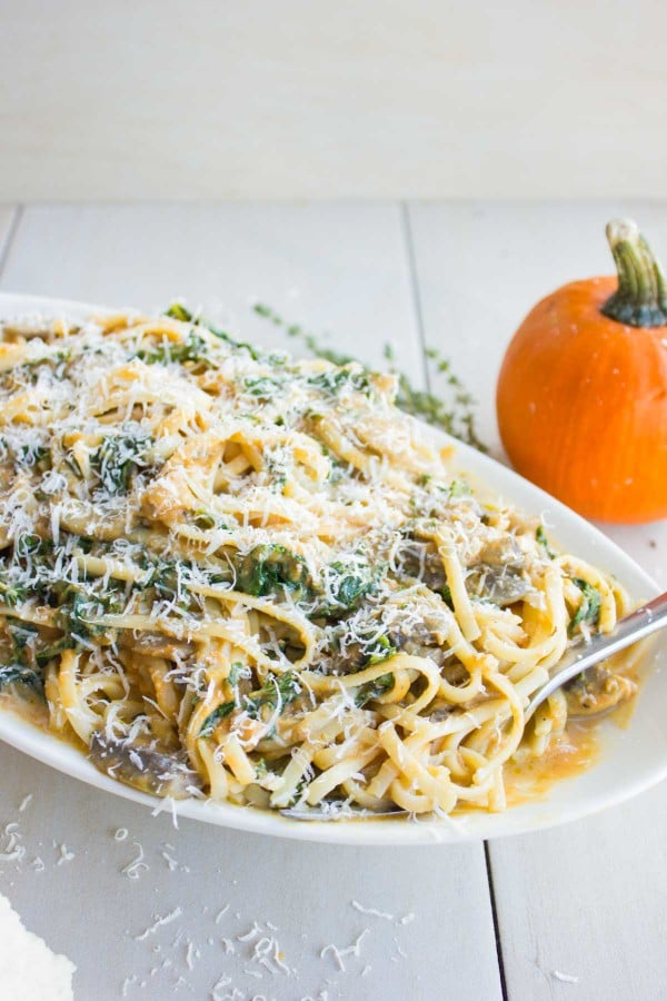 a big plate of Kale Mushroom Pumpkin Alfredo Pasta with parmesan grated on top