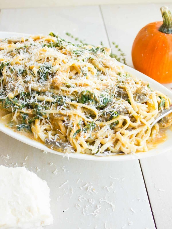 a plate of Kale Mushroom Pumpkin Alfredo Pasta with grated parmesan on top