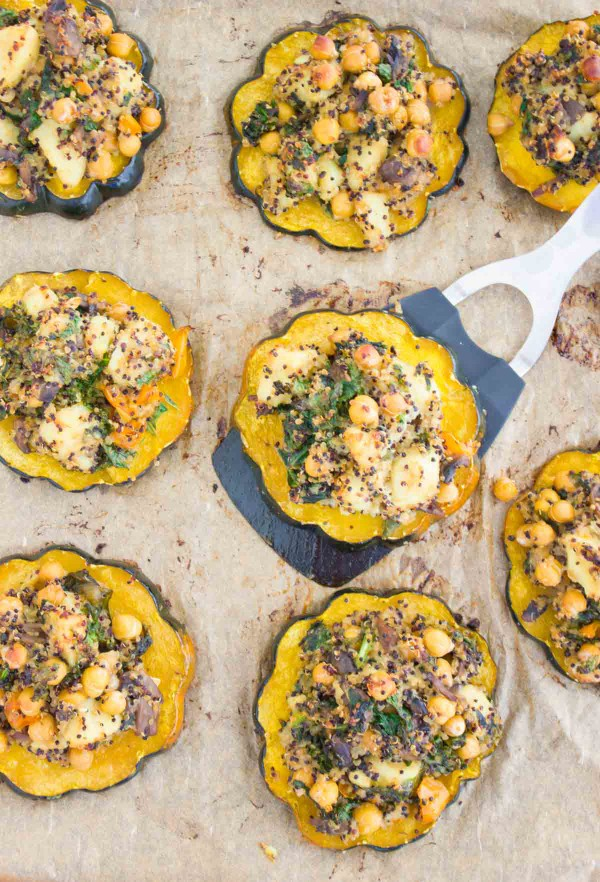 a baked acorn squash ring topped with Quinoa Kale Stuffing being lifted off a baking tray with more squash rings