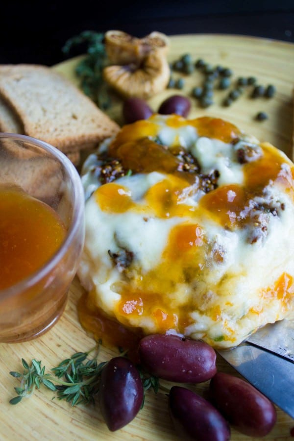 Baked Brie stuffed with Fig Olive Tapenade served on a wooden board with crackers and olives