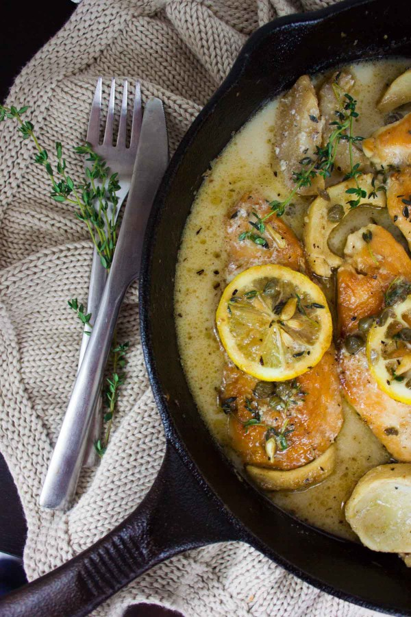 Lemon Caper Artichoke Chicken Piccata in a black skillet decorated with fresh thyme