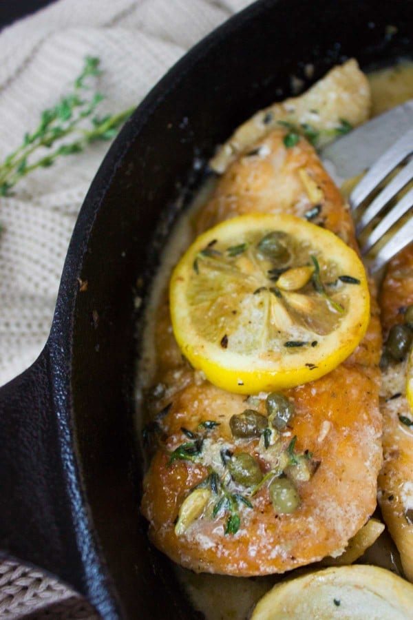 close-up of a piece of Lemon Caper Artichoke Chicken Piccata in a black skillet topped with a lemon slice
