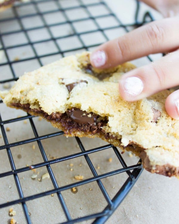 a hand reaching for half a Nutella-Stuffed Chocolate Chip Cookie on a cookie rack