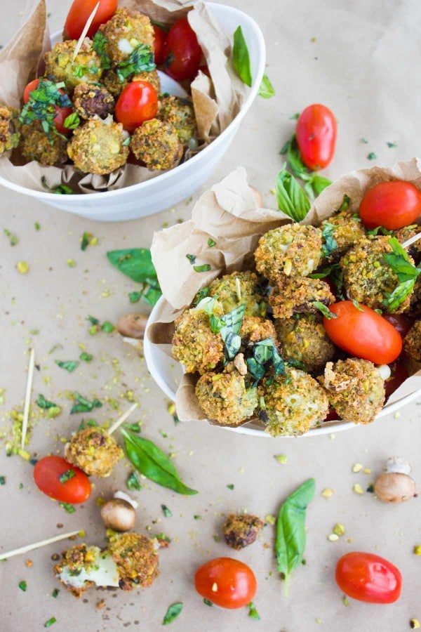 2 small oval bowls with Pistachio Fried Caprese Bites arranged with cocktail tomatoes
