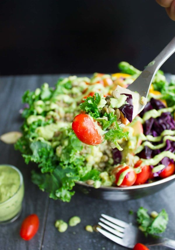 a fork full of Paleo Mexican Style Lentil Detox Salad balanced over a salad bowl