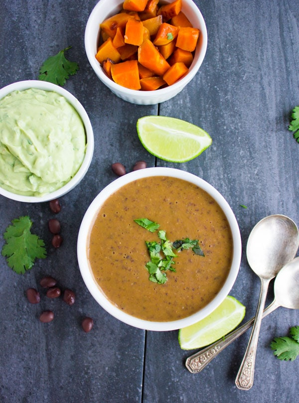 a bowl of Sweet Potato Black Bean Soup with avocado crema and roasted sweet potato cubes on the side