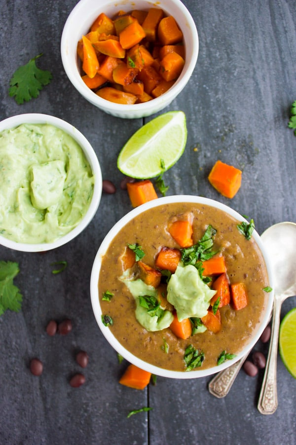 a bowl of Sweet Potato Black Bean Soup topped with cubes of roasted sweet potatoes and a dollop of avocado crema