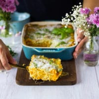 A hand holding a serving spoon serving up a slice of butternut squash lasagna on a wooden board
