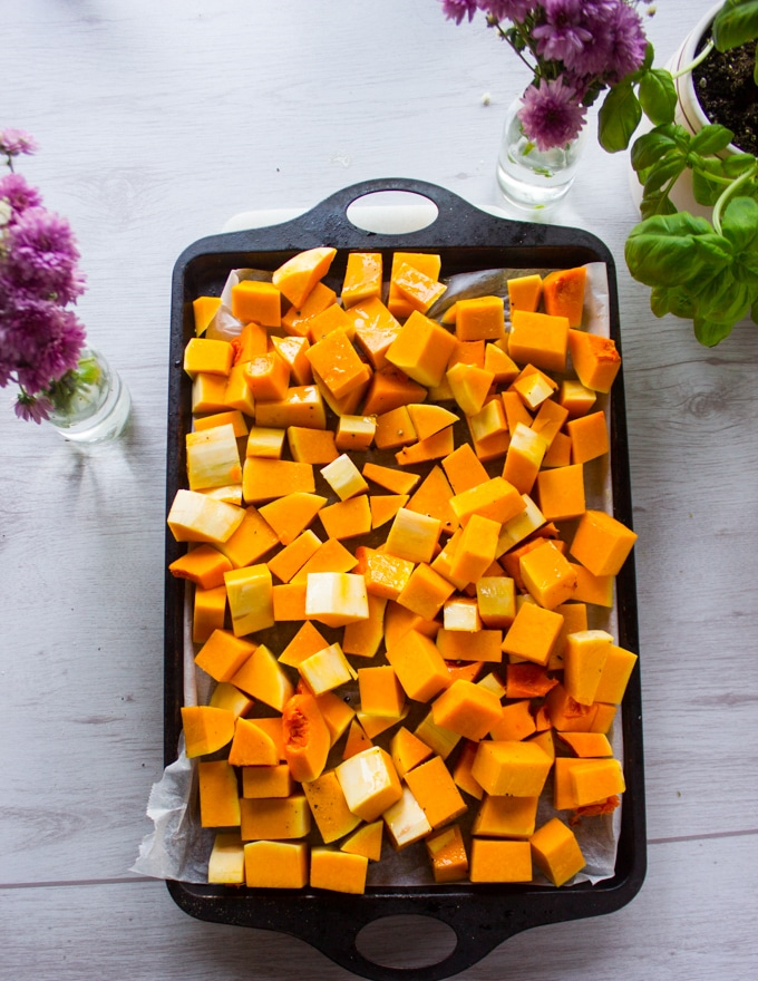 Butternut squash cut up into cubes and placed on a baking sheet, seasoned and ready for roasting